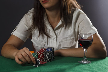 Young girl with a glass of wine playing poker