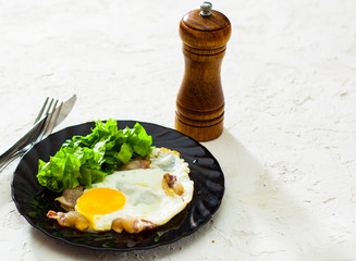 fried eggs with bacon and salad in black plate on white table