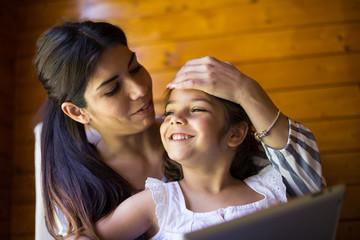 Crop view of brunette young mother and daughter sitting together on wooden background