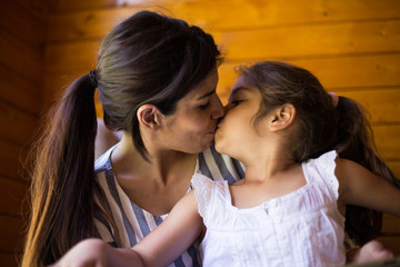 Crop view of young mother kissing little daughter on wooden panel background