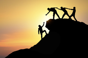 Assistance, teamwork and achievement concept. silhouette of man helping friend to success together