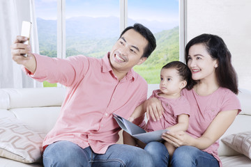 Smiling family taking selfie photo on sofa
