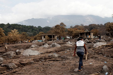 Eufemia Garcia, 48, who lost 50 members of her family during the eruption of the Fuego volcano, walk on top what use to be houses to find the area where it was her house and then search for her family in San Miguel Los Lotes