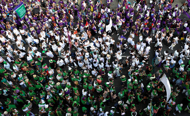 Women wear coloured clothes and march in a colour coordinated way to show the suffragette colours of green, white and violet - standing for Give Women Votes - in the 'Processions' women's march in London