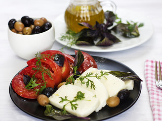 White cheese with tomatoes, green and black olives, basil, coriander and olive oil on a black plate