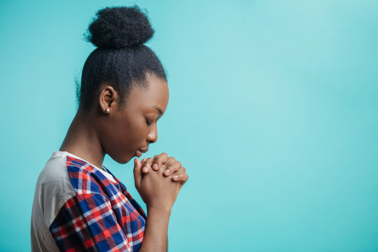 close up side view portrait of black girl with lively faith. expiatoryfaith. mixed race girl is asking forgiveness because she has done a lot of mistakes and sins. copyspace. profile