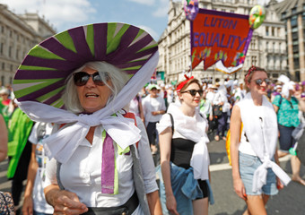 Women wear the suffragette colours of green, white and violet - standing for Give Women Votes - in the 'Processions' women's march in Westminster, London