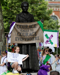 Demonstrators hold banners in the suffragette colours of green, white and violet - standing for Give Women Votes - next to the statue of Millicent Fawcett during the 'Processions' women's march in Westminster, London