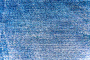 Texture of a fabric of a blue piece of jeans trousers