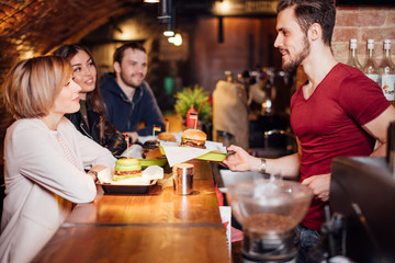 Group of happy smiling friends ordering food through barkeeper at the counter in modern restaurant with loft style, bricks and pipes, interior