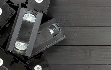 old video tape on black wooden background. top view