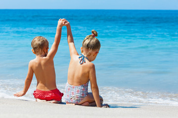 Happy kids have fun in sea surf on white sand beach. Couple of children sit in water pool with hands up. Travel lifestyle, swimming activities in family summer camp. Vacations on tropical island