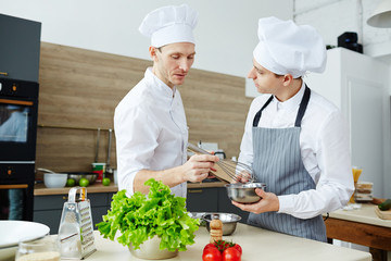 Chef with whisk mixing raw eggs in steel bowl while consulting his trainee in the kitchen