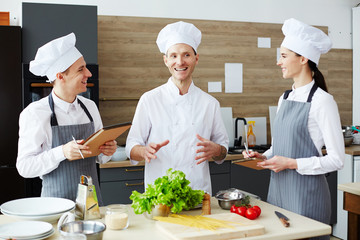 Young master and two trainees discussing cooking procedure by workplace