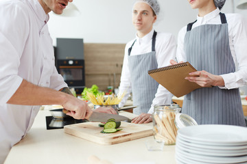 Woman in apron making cooking notes in notepad while chef slicing cucumber on wooden board