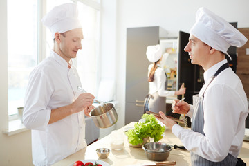 One of trainees talking to chef while making notes about healthy and tasty food