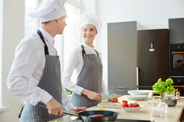 Two young trainees in chef caps and aprons consulting during process of cooking