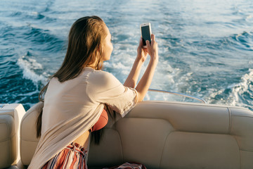 a young rich girl sails on her yacht on the Caribbean sea, takes pictures of the landscape