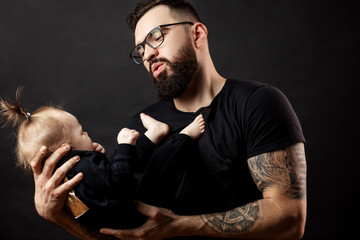 Happy handsome father in perfect fit, looking at his infant baby girl in his hands, fondling and nursing her tenderly over black background.