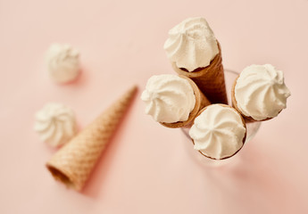 waffle sweet cone with white sweets meringue over pastel light pink background, top view. Spring mood concept, birthday, breakfast or tasty treat