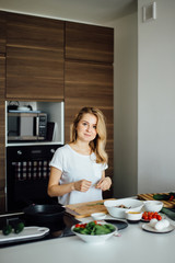 Young positive girl, recently got married , learning to cook home made meal from fresh and healthful diet products. Blonde woman looking at camera at kitchen background.
