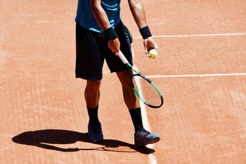 Professional tennis player playing a game of tennis on a court. He is about to hit the ball with the racket. The ball is suspended in the air..