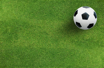 Soccer football ball on green grass of soccer field background.