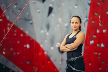 Portrait of strong athletic brunette female climber in black outfit with protective gear over artificial painted rock background.