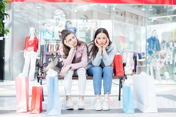 Sad exhausted attractive student girls tired from shopping sitting on bench with abundance of colorful paper bags in mall
