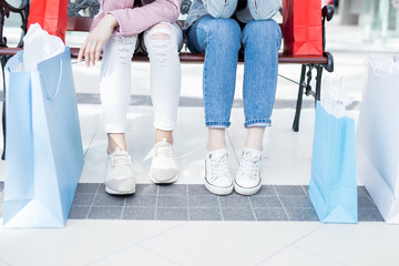 Close-up of unrecognizable teenage girls in sneakers sitting on bench and resting after purchases in stores of shopping mall