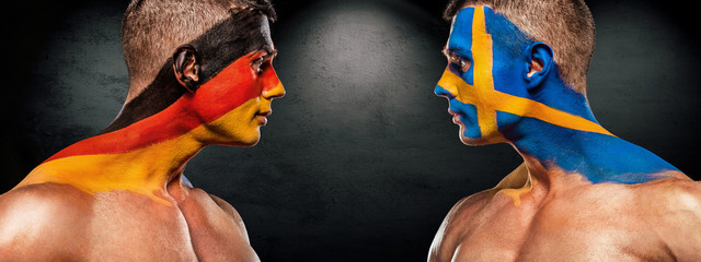 Deutschland vs Sverige. Two soccer or football fans with flags face to face on stadium.