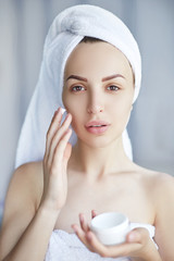 Spa Woman applying Facial Cream. Beauty Treatments. Portrait of beautiful girl with a towel on her head applying facial cream. Cosmetology.