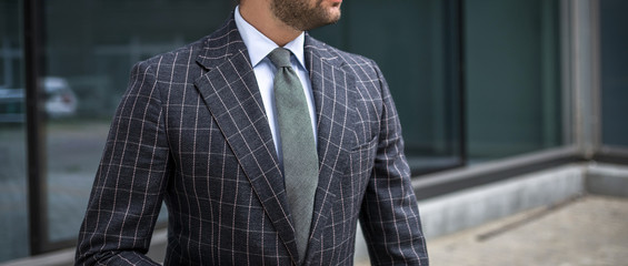 Man in custom tailored business suit posing outdoors