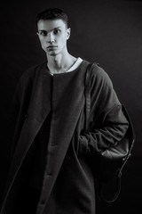 Monochrome portrait of caucasian man in casual outfits wear coat and leather bag standing over gray grunge background with space, lifestyle traveler, beauty and fashion concept