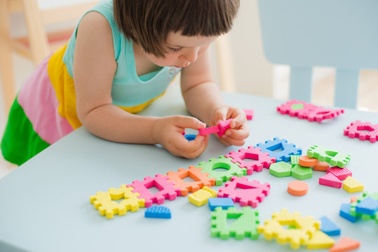 little girl playing at a children's table with a puzzle, early education. Bright soft blocks
