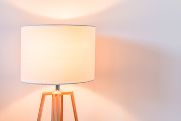 Modern bedroom lamp lit against white wall with copy space - close-up
