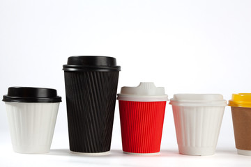 Row of coffee cups with lids on white background with copy space