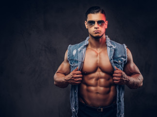 Sexy naked fashionable athletic man in a denim vest and sunglasses poses in a studio.