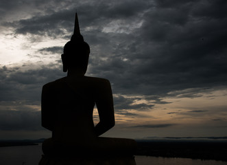 Black budha silhouette with dark cloud on background