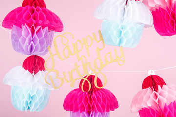 Paper cupcakes celebration decoration with happy birthday lettering. Holiday party concept