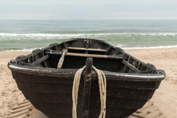 Frontansicht eines schwarzen Holzfischerbootes, Meer im Hintergrund und Copyspace