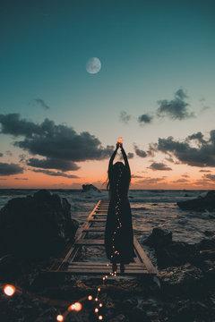 Sagoma di una giovane bella ragazza sogna felice amore in riva al mare dopo il tramonto