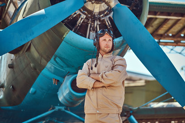 Valiant handsome pilot in a full flight gear standing with crossed arms near military airplane.