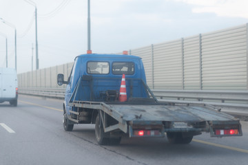 Tow truck on the highway with metal safety barrier and acoustic wall