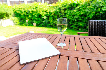 Mockup of a magazine cover on a wooden table in the garden in summer