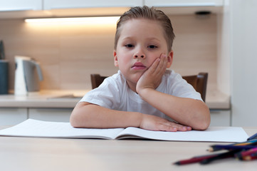 Little thoughtful boy sits at table during coloring with pencils and looks into the camera thinking about something