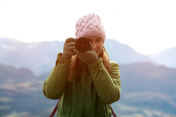 Charming young positive woman in autumn clothes with camera in hands while traveling through beautiful natural places. Concept of travel