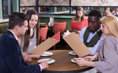 Happy people discussing restaurant menu