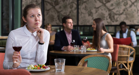 Unhappy young woman alone in restaurant