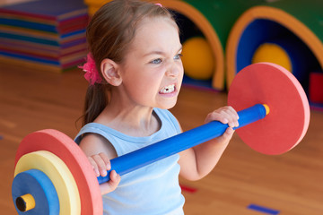 A child in the gym raises the bar.